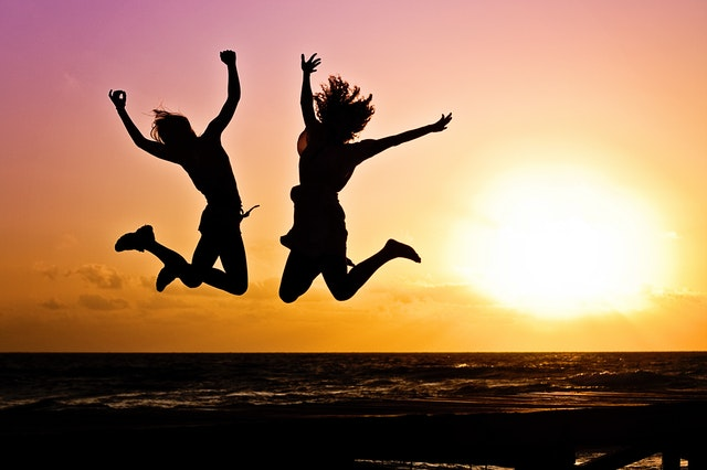 Two chiropractic patients jumping with joy at sunset